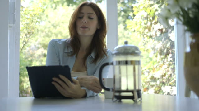 woman using digital tablet while drinking coffee. - brown hair stock videos & royalty-free footage