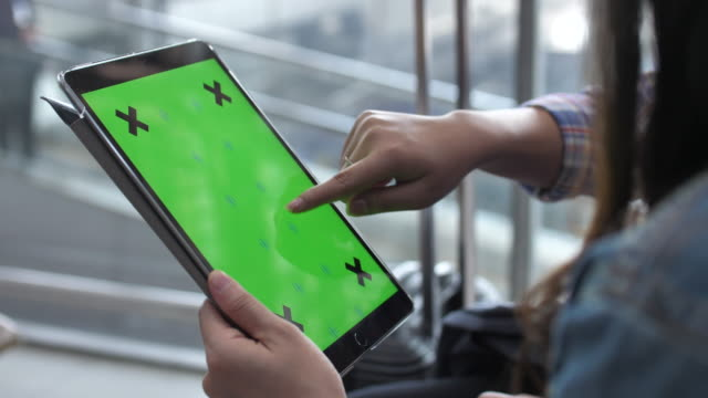 Woman using Digital Tablet with Green Screen in Vertical