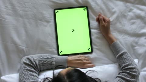 kvinna använda digital tablett med grön skärm på sängen, hög vinkel view, vertikal - skrivbord bildbanksvideor och videomaterial från bakom kulisserna