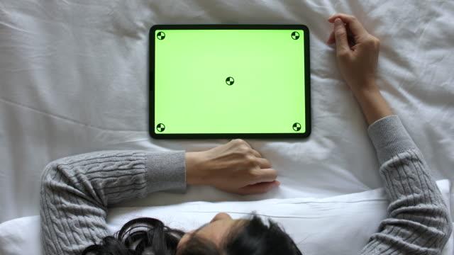 vidéos et rushes de femme utilisant la tablette numérique avec l'écran vert sur le lit, vue de haut angle, horizontal - back lit