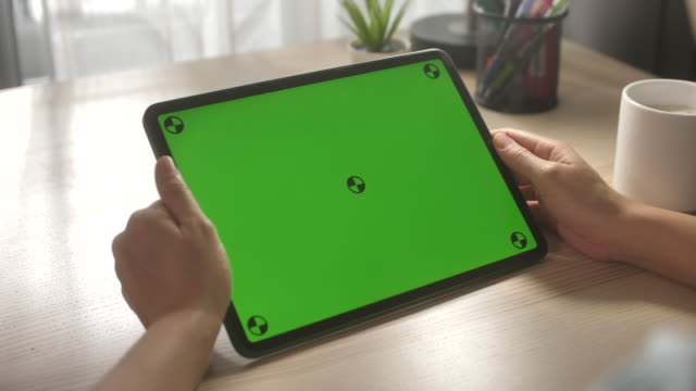 frau mit digitaltablett mit grünem bildschirm - über die schulter stock-videos und b-roll-filmmaterial