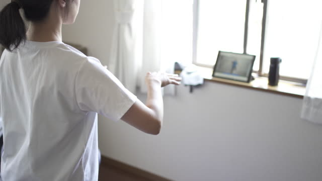 vidéos et rushes de femme utilisant des tablettes numériques pour faire l'entraînement de forme physique à la maison - hygiène de vie
