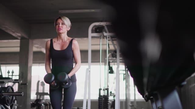 vidéos et rushes de femme à l'aide d'haltères pour exercice à la salle de fitness. - quête de beauté