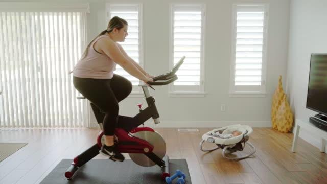 家庭でエクササイズバイクを使用している女性 - 大柄点の映像素材/bロール