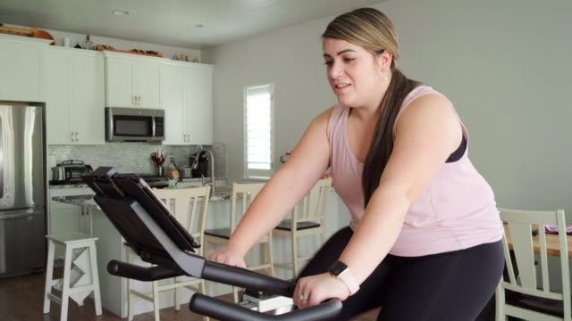 woman using exercise bike in a home - body positive stock videos & royalty-free footage