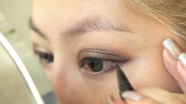 woman using eyeliner makeup beauty