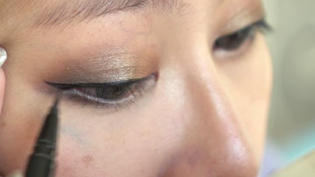 woman using eyeliner makeup beauty