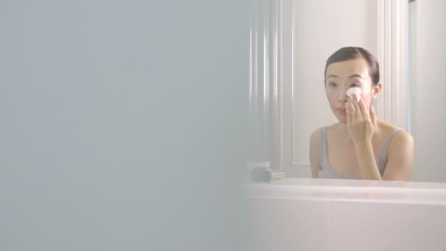 woman using face cleanser  - mirror点の映像素材/bロール