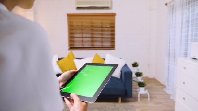 家庭でのリビングルームでのエアコンのホームコントロールにグリーンスクリーンタブレットアプリを使用して女性。スマートホームオートメーション制御コンセプト - エアコン点の映像素材/bロール