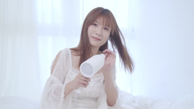 vídeos y material grabado en eventos de stock de mujer usando secador de pelo después de la ducha - pueblos de asia oriental