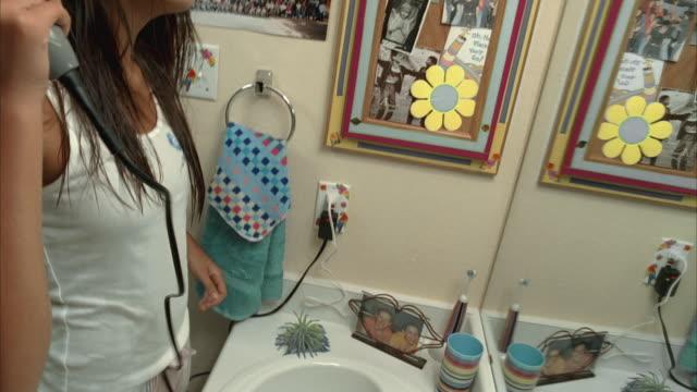 MS TU SLO MO Woman using hair dryer in bathroom / Kyle, Texas, USA