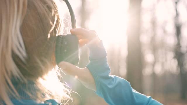 vídeos y material grabado en eventos de stock de slo mo woman usando auriculares en su cabeza mientras está en el bosque - auriculares una persona escapismo vista posterior cabeza y hombros