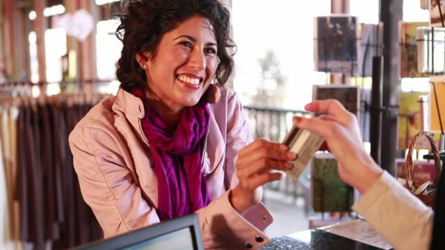 ms woman using her credit card to purchase items at boutique / sante fe, new mexico, usa - acquisto con carta di credito video stock e b–roll