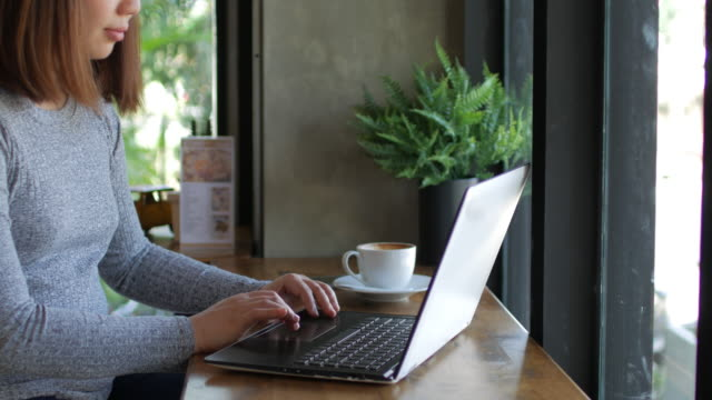Woman using her laptop at relaxing time in coffee cafe , dolly shot