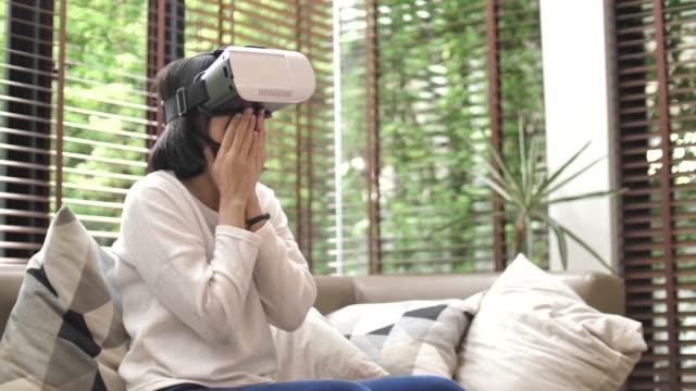 自宅で彼女の携帯電話の vr ヘッドセットを使用して女性 - 仮想空間点の映像素材/bロール