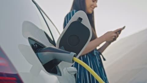 vídeos y material grabado en eventos de stock de slo mo woman usando su teléfono móvil mientras carga su coche eléctrico por energía solar - coche híbrido