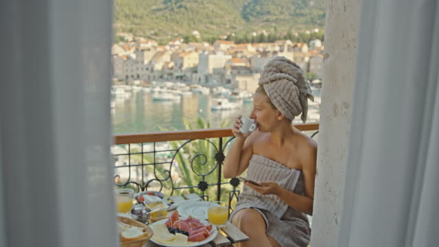 vídeos de stock e filmes b-roll de slo mo woman using her mobile phone while having breakfast on the balcony by the sea - mid adult women