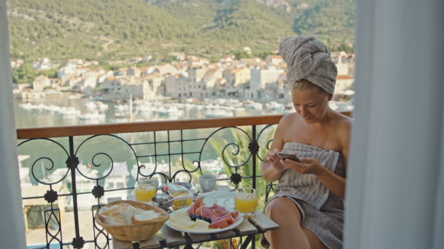 slo mo woman using her mobile phone while having breakfast on the balcony by the sea - food and drink stock videos & royalty-free footage