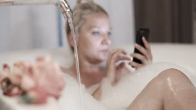 slo mo woman using her mobile phone while taking a bubble bath - bath stock videos & royalty-free footage