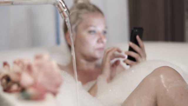 slo mo frau mit ihrem handy während der einnahme eines blasenbades - badewanne stock-videos und b-roll-filmmaterial