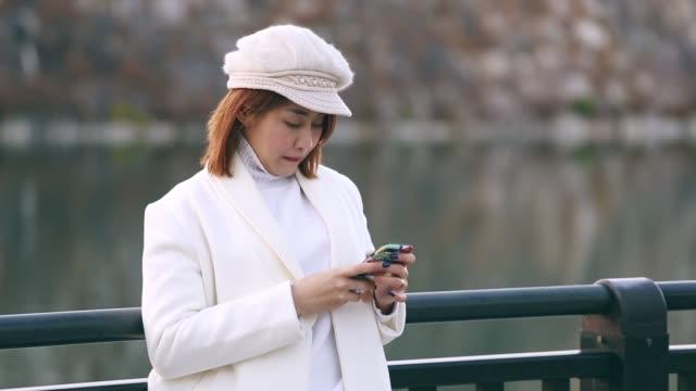 大阪府の公共の公園で湖の彼女のスマート フォンだけで、日没をしている女の人 - 負の感情点の映像素材/bロール