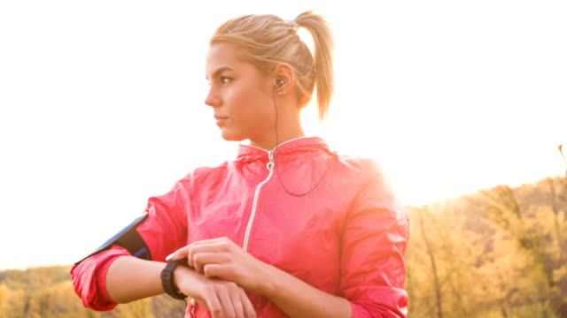 Woman using her smart watch while jogging in nature