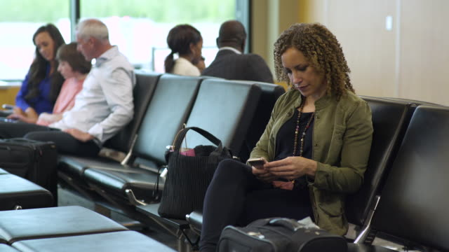 Woman using her smartphone at an airport