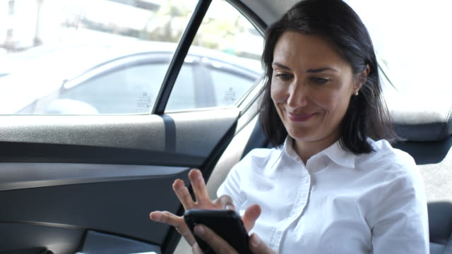 woman using her smartphone in back seat of moving car - taxi stock videos & royalty-free footage