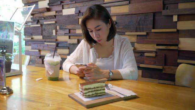 woman using her smartphone in cafe - organizzatore elettronico video stock e b–roll
