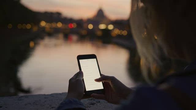 夕暮れ時にサンタンジェロ橋の向かいの橋の上でスマートフォンを使用してslo mo女性 - サンタンジェロ橋点の映像素材/bロール