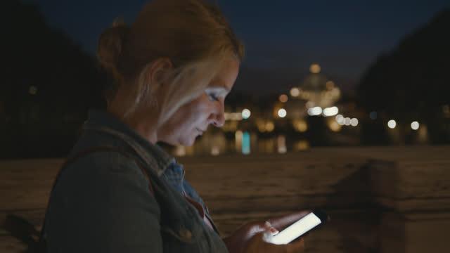 夜にサンタンジェロ橋の向かいの橋の上で彼女のスマートフォンを使用してslo mo女性 - サンタンジェロ橋点の映像素材/bロール