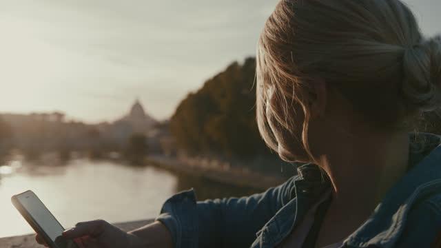 日没時にサンタンジェロ橋の向かいの橋の上でスマートフォンを使用してslo mo女性 - サンタンジェロ橋点の映像素材/bロール