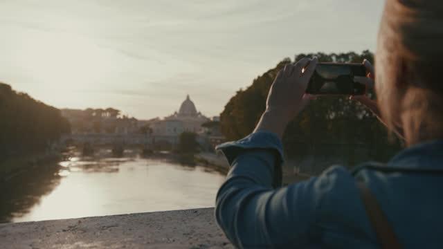 日没時にサンタンジェロ橋の写真を撮るために彼女のスマートフォンを使用してslo mo女性 - サンタンジェロ橋点の映像素材/bロール