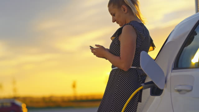 slo mo woman using her smartphone while charging a car at sunset - mode of transport stock videos & royalty-free footage