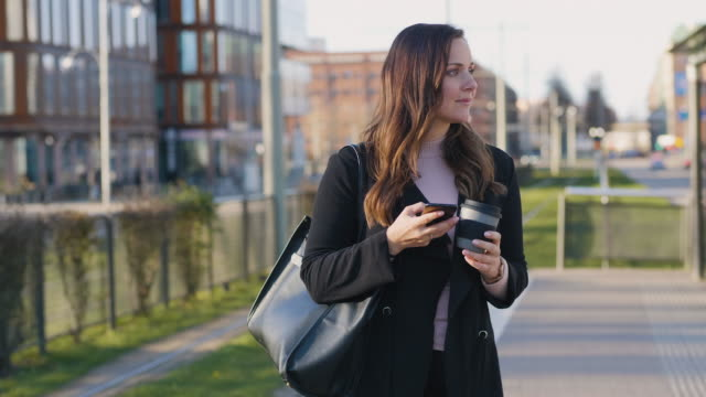 woman using her smartphone while waiting for the cable car - bus stop stock videos & royalty-free footage