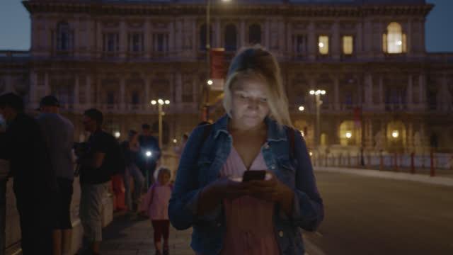 夜にローマの橋を渡って歩いている間、彼女のスマートフォンを使用してslo mo女性 - サンタンジェロ橋点の映像素材/bロール