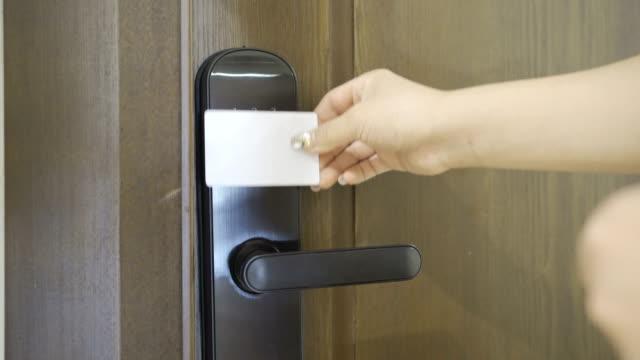 vídeos de stock, filmes e b-roll de mulher usando cartão-chave na fechadura da porta - indústria eletrônica