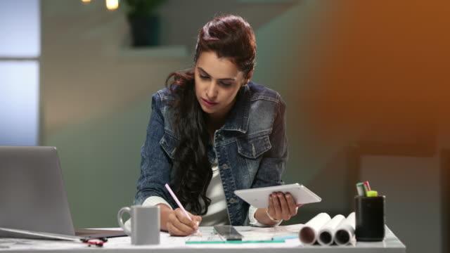 vídeos de stock, filmes e b-roll de ms woman using laptop and digital tablet while writing on paper / delhi, india - jaqueta jeans