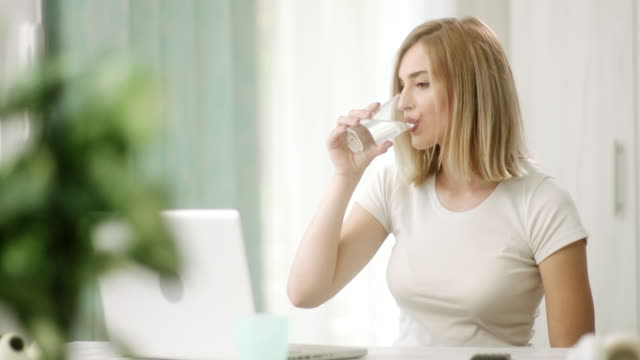 woman using laptop and drinking water - blonde hair stock videos & royalty-free footage