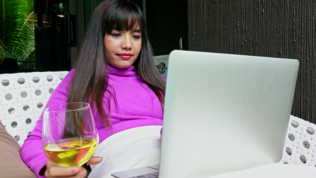 woman using laptop and drinking white wine in balcony - 25 29 years stock videos & royalty-free footage