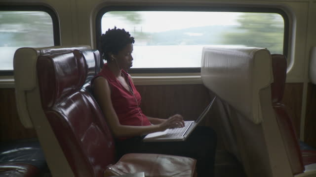 WS Woman using laptop and mobile phone and listening to music on portable media player in moving commuter train / New York City, New York, USA