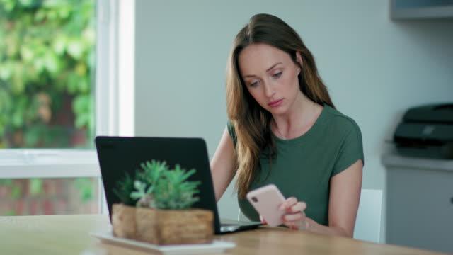 vídeos de stock e filmes b-roll de woman using laptop and phone - secretária temporária