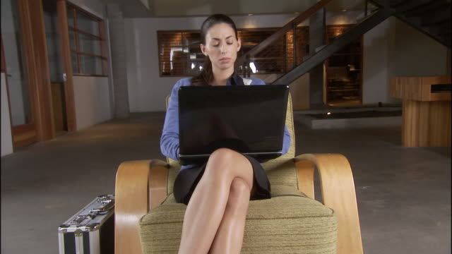 ms woman using laptop and sitting in chair in sparse office / los angeles, california, usa - haar nach hinten stock-videos und b-roll-filmmaterial