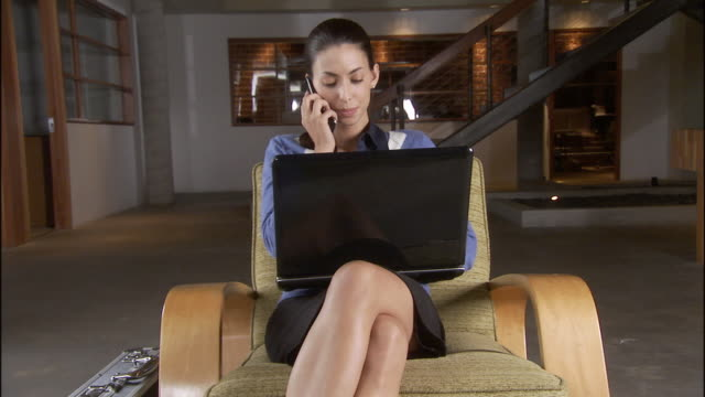 cu zo ms woman using laptop and talking on cell phone while sitting in chair in sparse office / los angeles, california, usa - haar nach hinten stock-videos und b-roll-filmmaterial