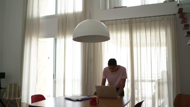 vídeos y material grabado en eventos de stock de mujer usando portátil en casa - una sola mujer joven