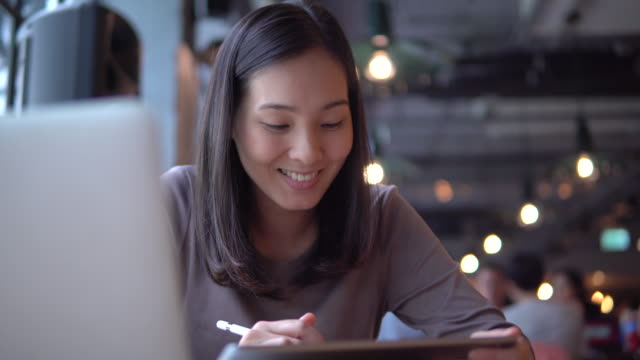 woman using laptop at indoor cafe - south east asia stock videos & royalty-free footage