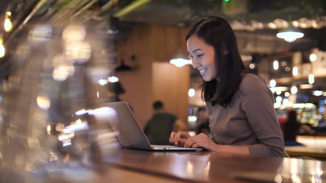 woman using laptop at night in cafe - laptop video stock e b–roll
