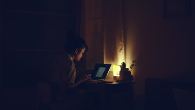 woman using laptop at night - overworked stock videos & royalty-free footage