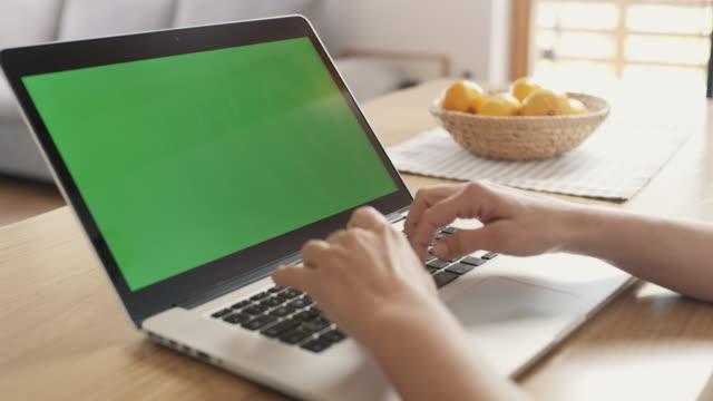 vídeos de stock, filmes e b-roll de ms woman usando o laptop na mesa - foco difuso