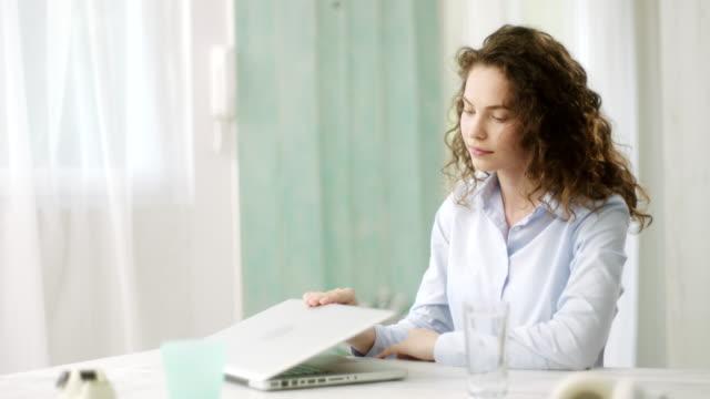 Woman using laptop, closing him down and looking at camera